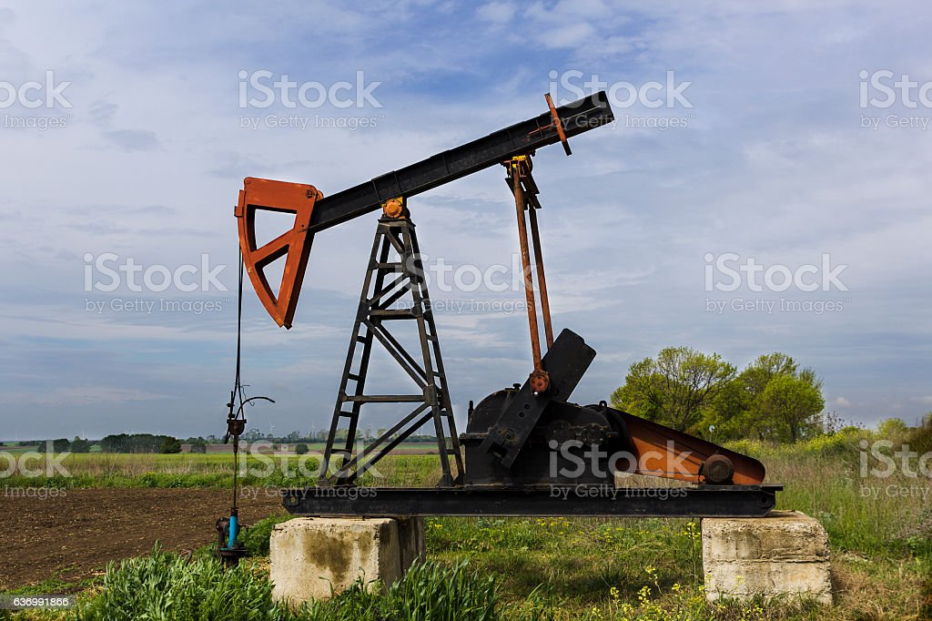 Oil derrick pumps petroleum on the field stock photo
