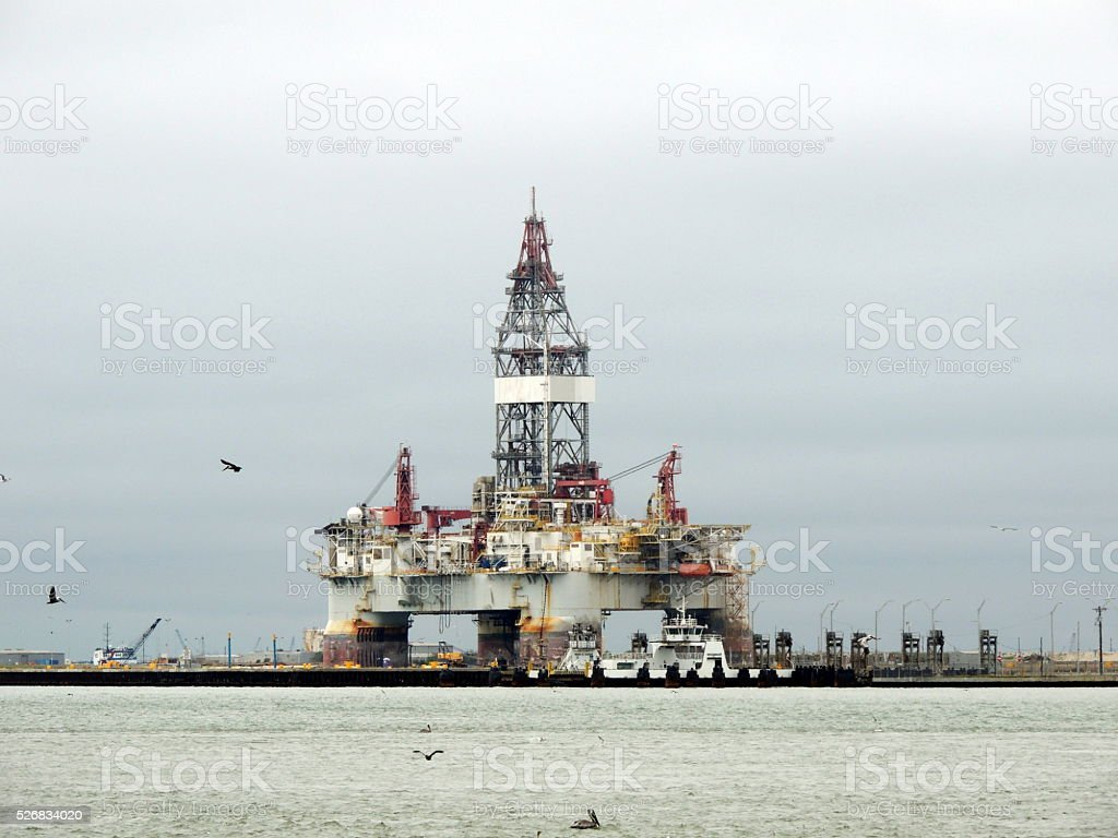 Oil Drilling Rig or platform with pelicans flying past stock photo