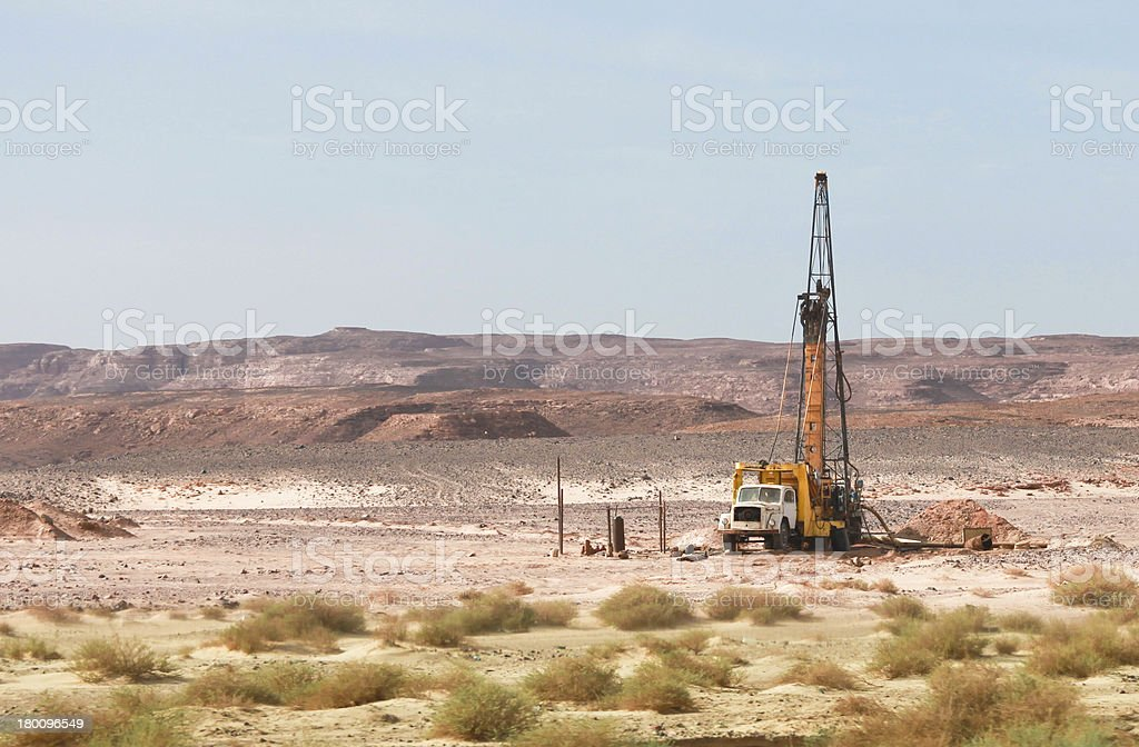 Oil drilling well alone in the middle of sandy desert stock photo