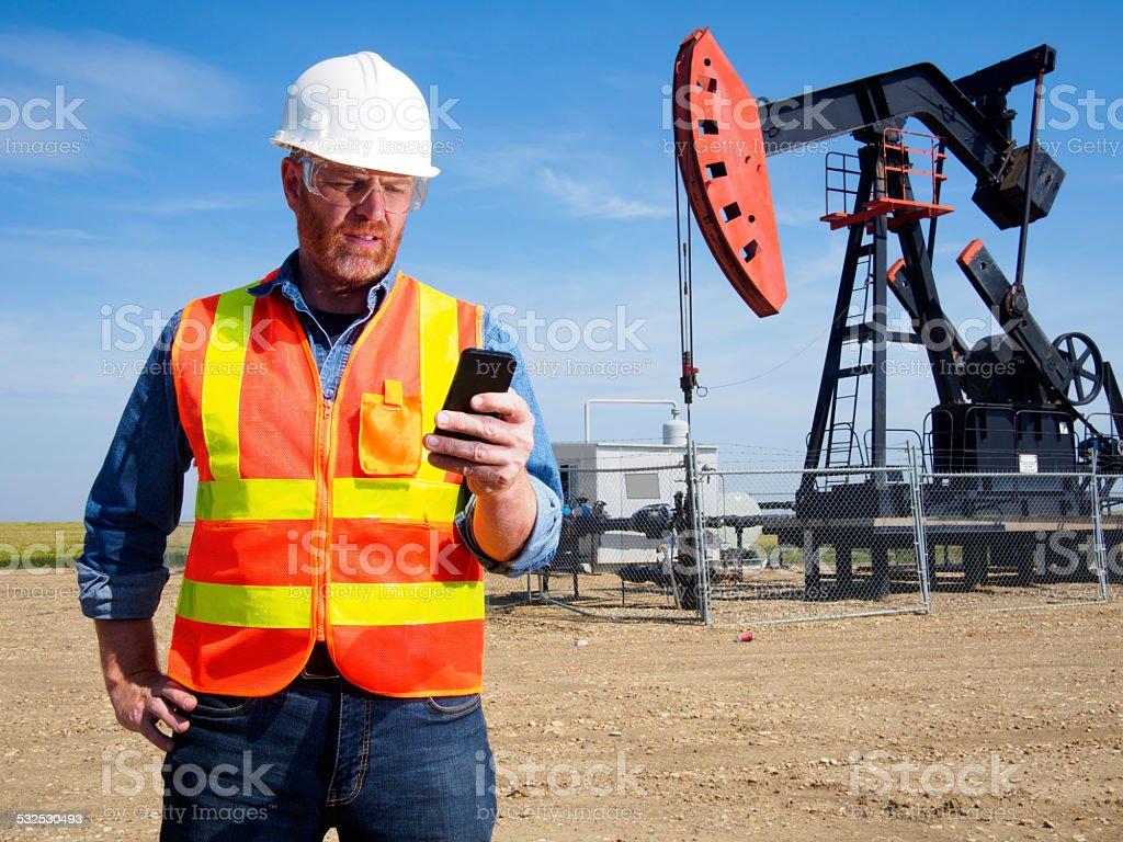 Oil Engineer and Smart Phone Technology stock photo