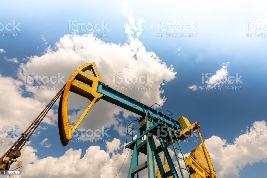Oil field with pump jack, profiled on blue sky with white clouds, on a sunny day stock photo