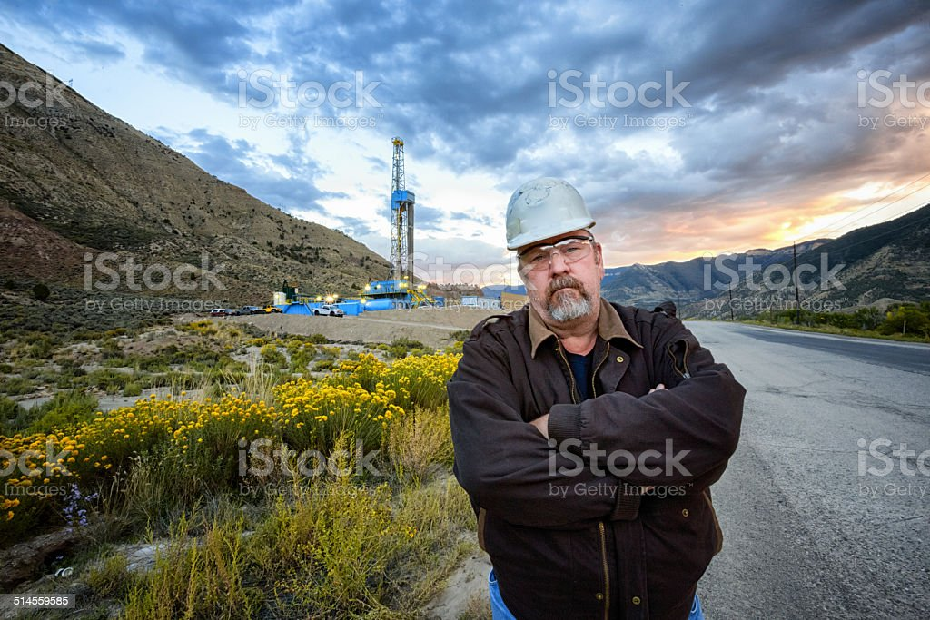Oil Field Worker and Fracking Drill Rig stock photo