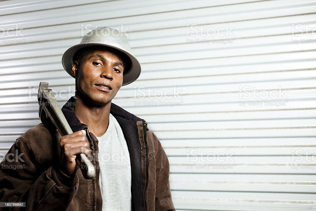 Oil Field worker carrying wrench wearing hardhat and jacket royalty-free stock photo