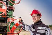 Oil field worker near wellhead valve