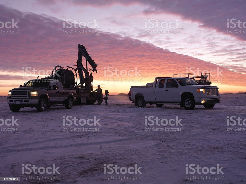 Oil Field Workers at Sunrise stock photo