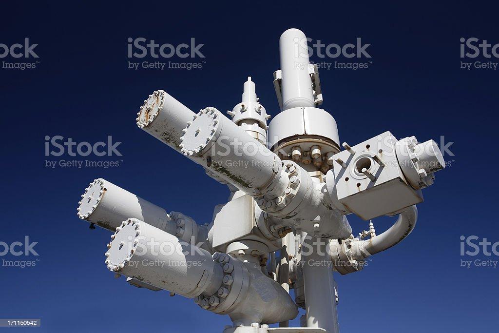 oil industry wellhead equipment pressure valves against blue sky stock photo