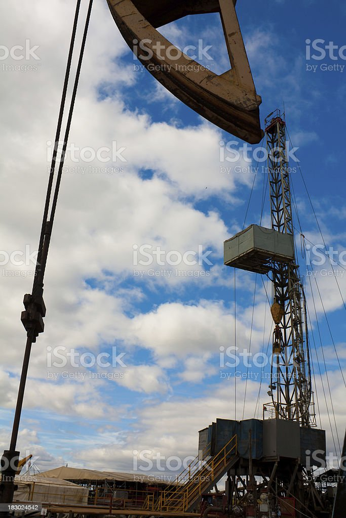oil jack close up and drilling rig behind it royalty-free stock photo