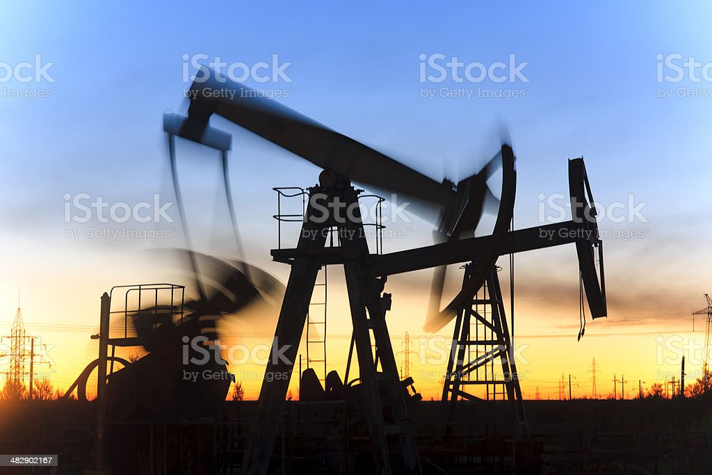 Oil jack silhouette in motion during beautiful sunset royalty-free stock photo