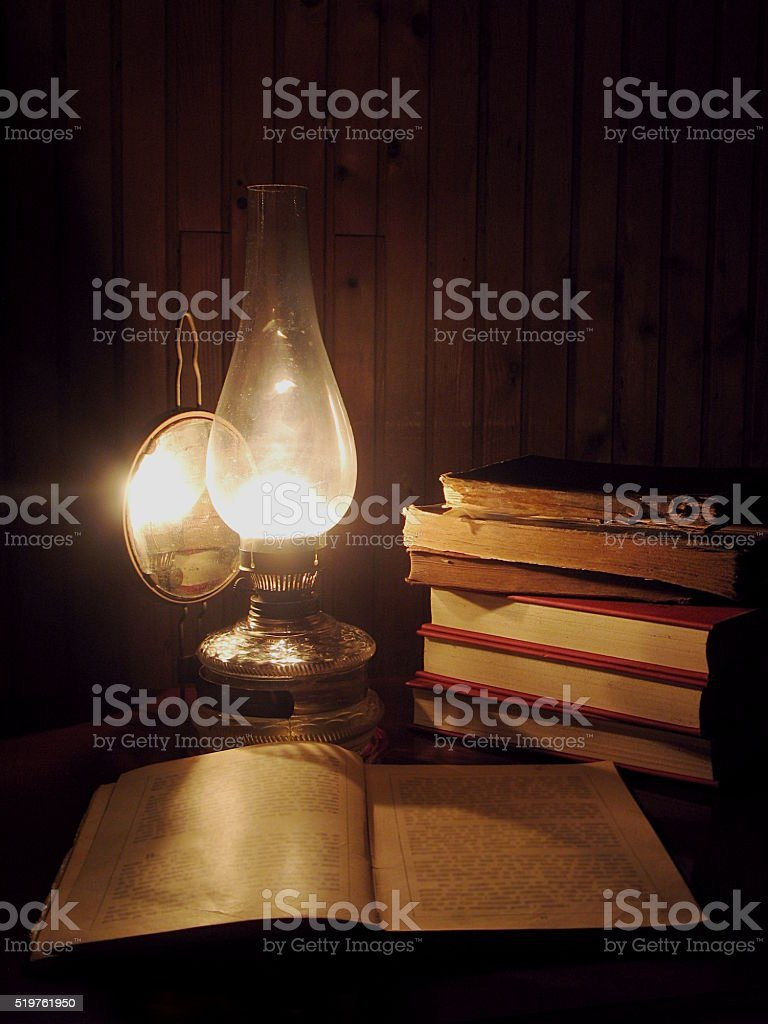 Oil lamp and old books stock photo