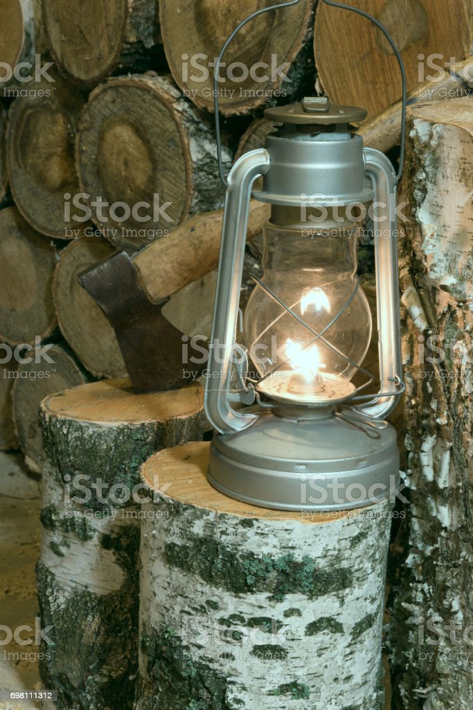 Oil lamp, ax and firewood in the barn stock photo