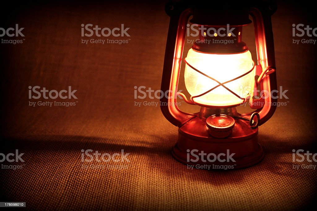 Oil lamp on a burlap and burning in dark. stock photo