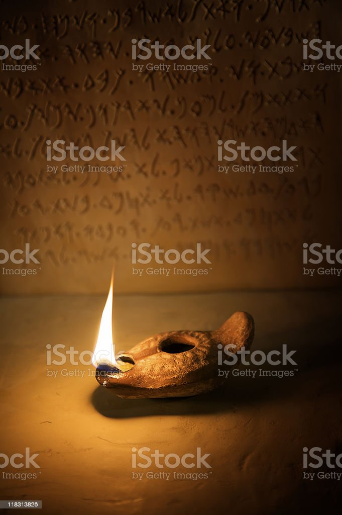 Oil Lamp with Ancient Inscription in Background stock photo