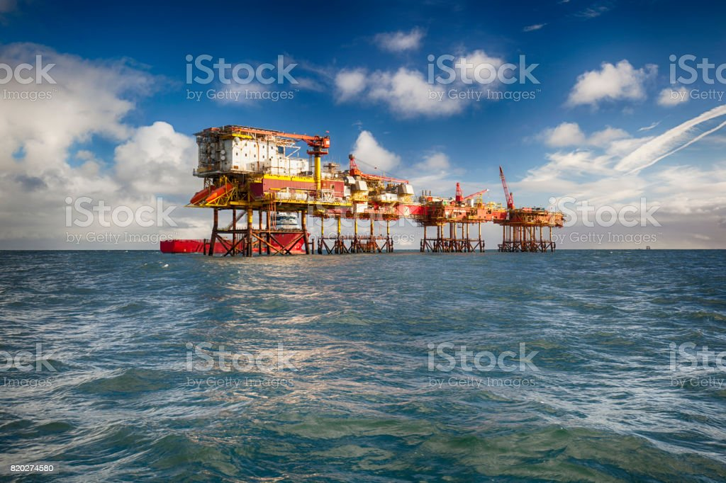 HDR Oil platform and supply ship at day stock photo