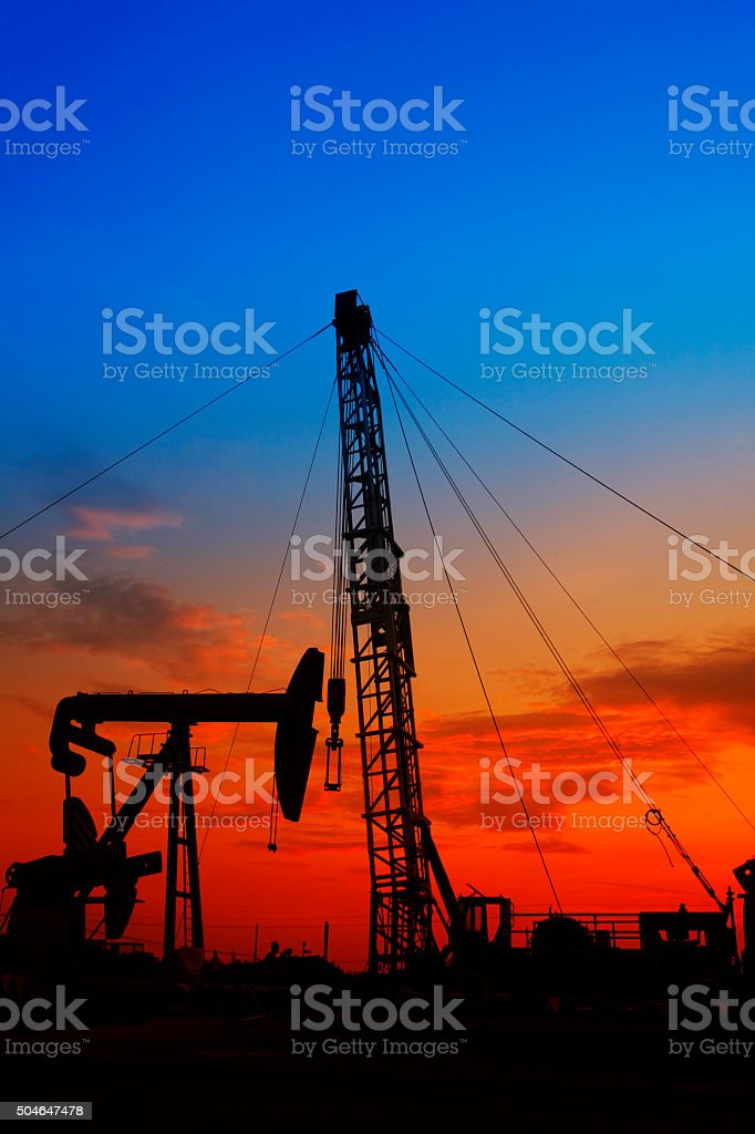 Oil pump and the silhouette of oilfield derrick stock photo
