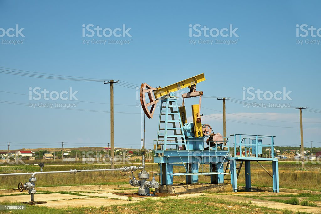 Oil pump jack in operation. royalty-free stock photo