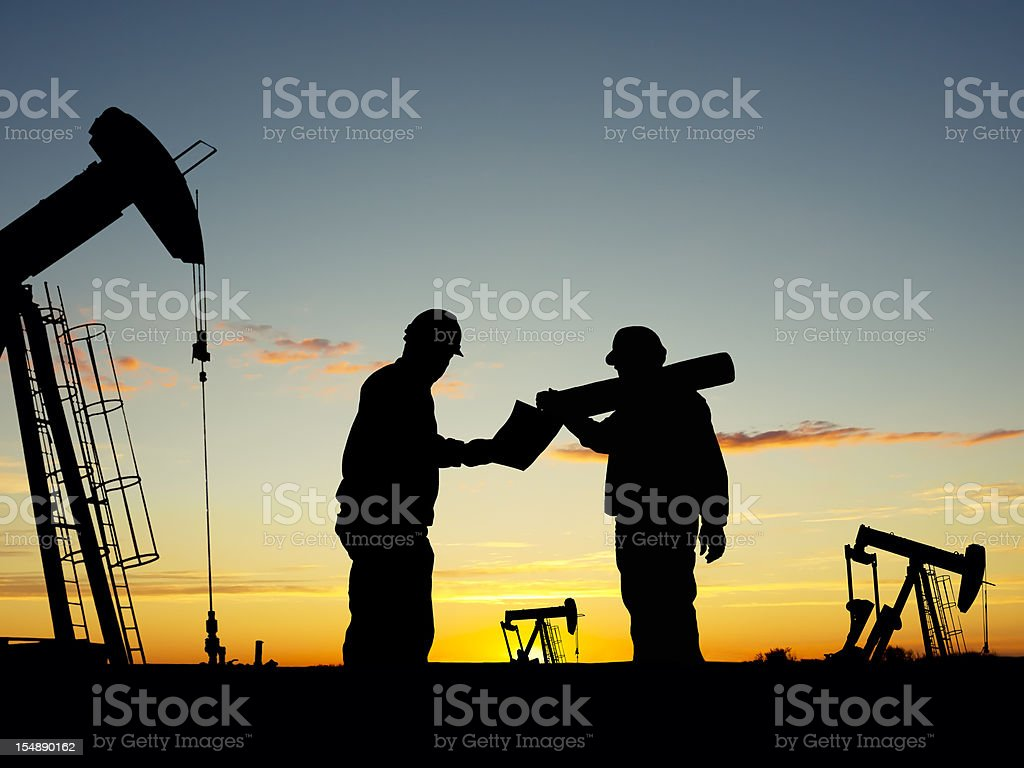Oil Pump Pumpjacks & Worker Silhouettes royalty-free stock photo