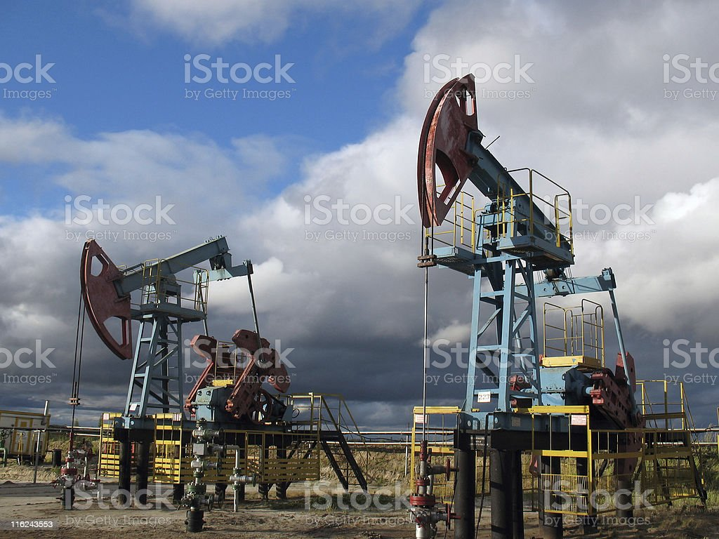 Oil pumps at work under a cloudy sky royalty-free stock photo
