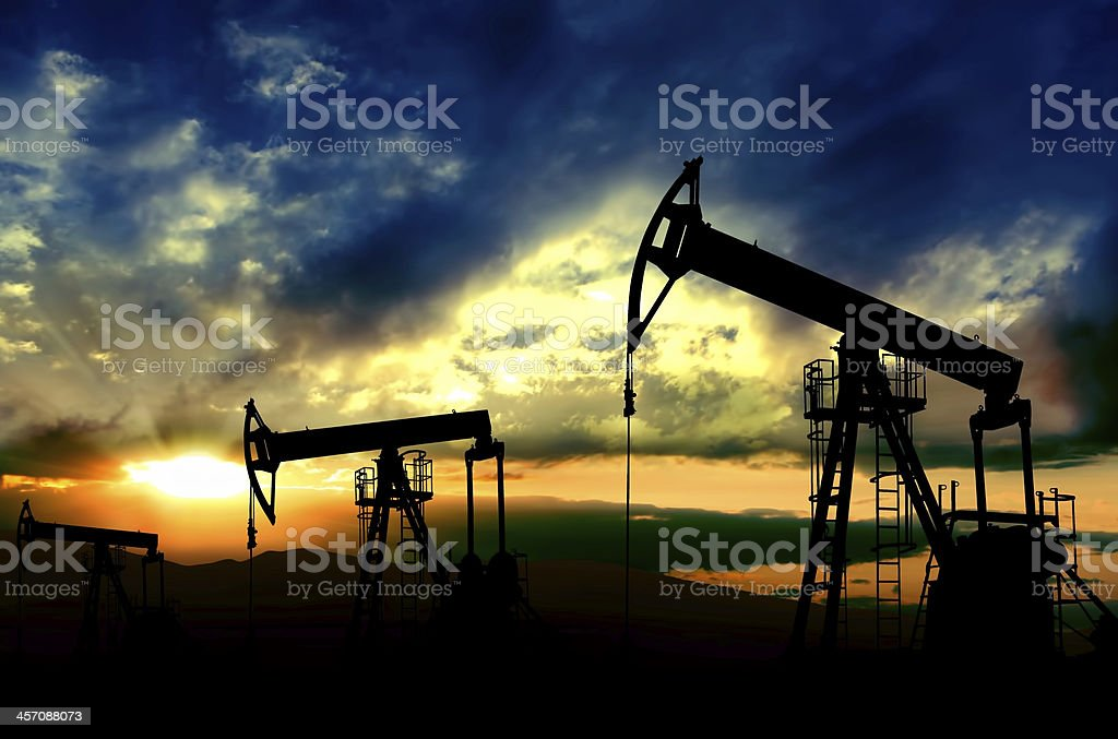 Oil pumps working on sunset background stock photo