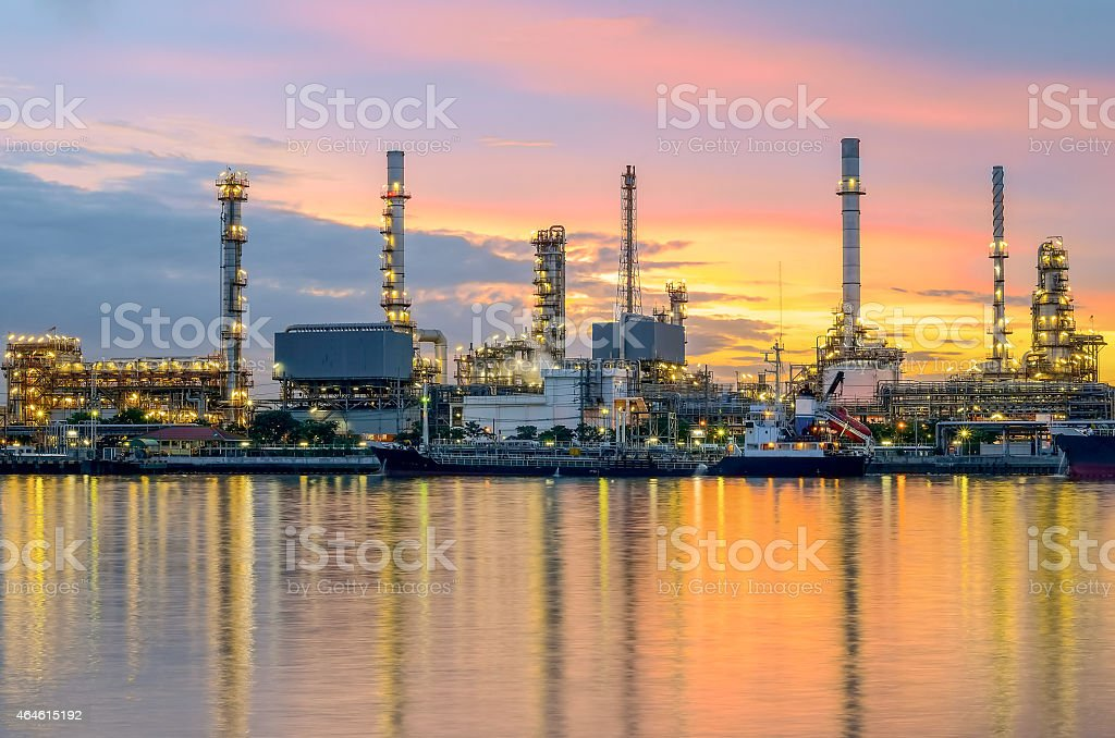 Oil refinery at twilight casting reflection onto water stock photo