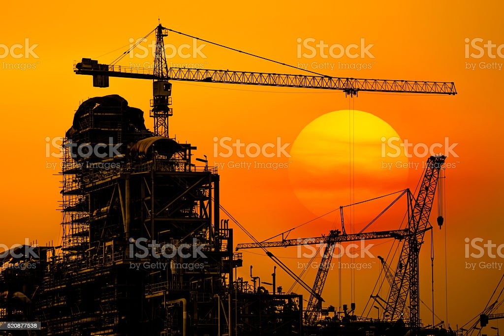 Oil refinery construction in silhouette, Industrial Oil refinery in building stock photo