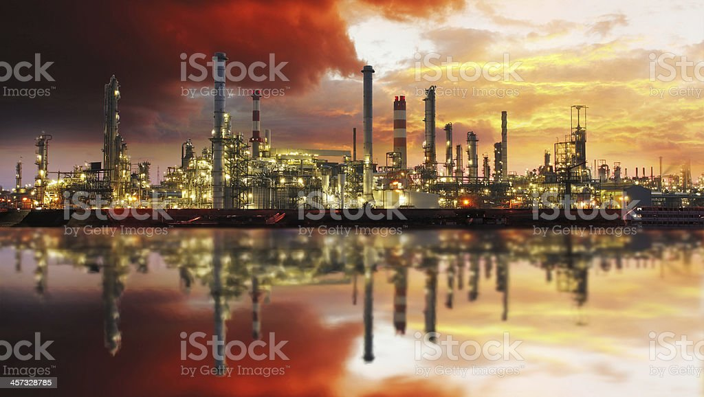 Oil refinery plant on water at sunset with a red sky stock photo