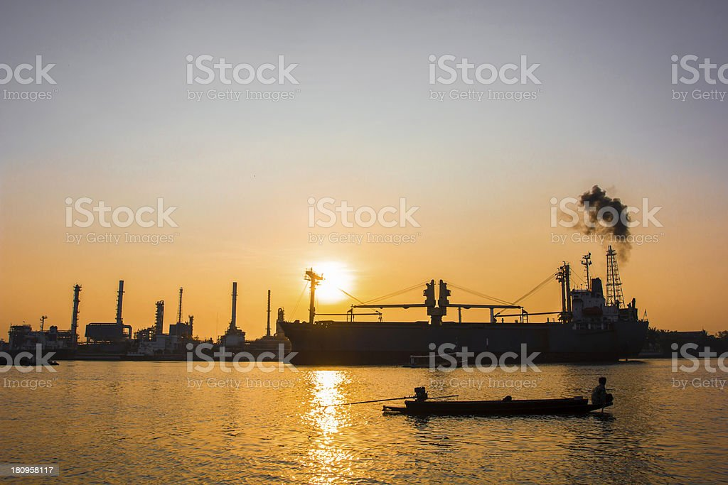 Oil refinery view and freighter with Sunrise royalty-free stock photo