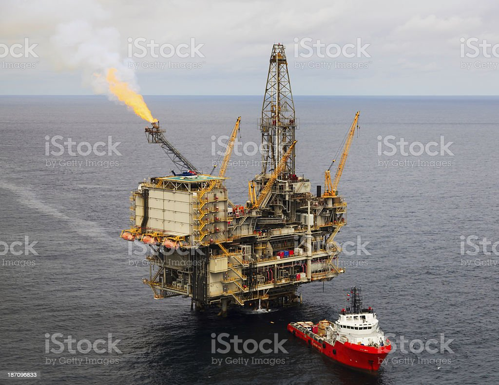 Oil Rig and Supply Boat stock photo