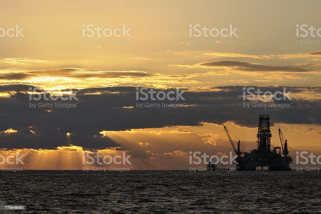 oil rig and vessel at sunrise royalty-free stock photo