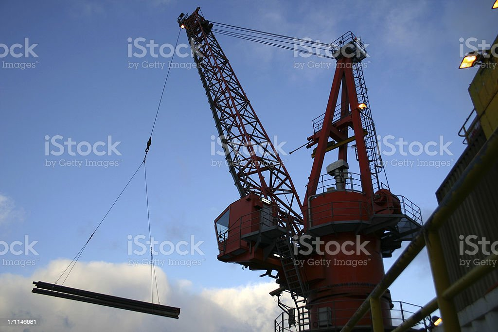 oil rig crane lifting drill pipe from a boat stock photo