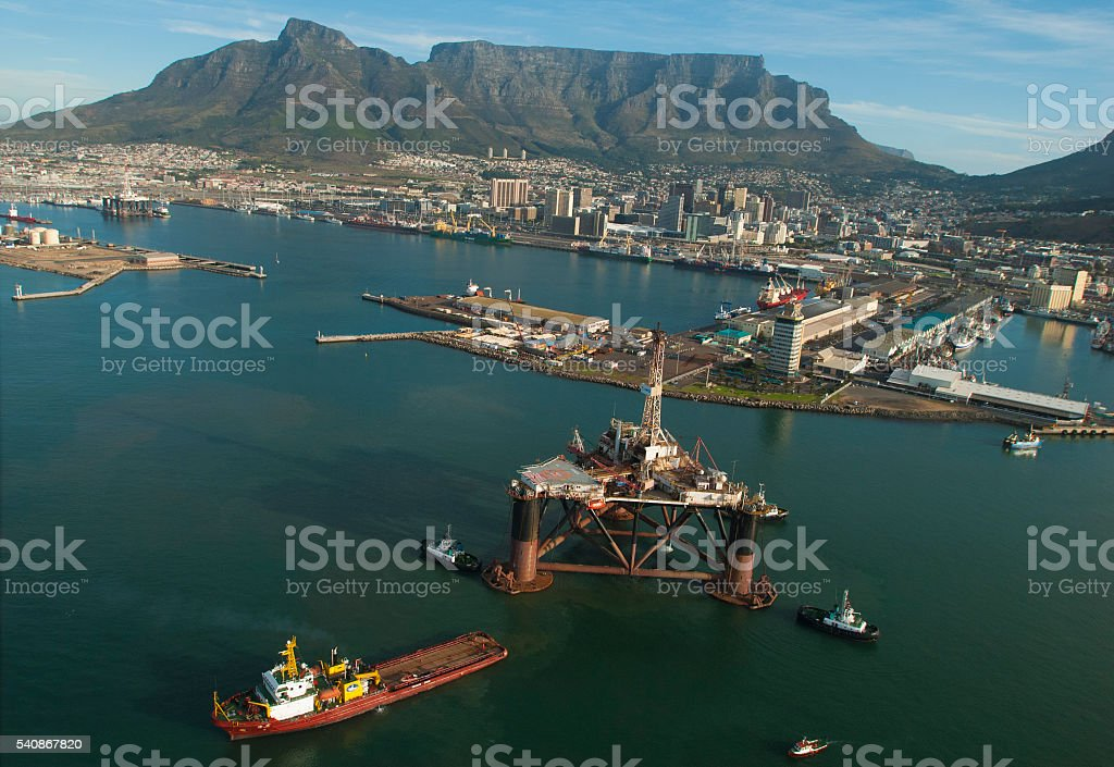 Oil rig  escorted out of Cape Town harbour by tugs stock photo