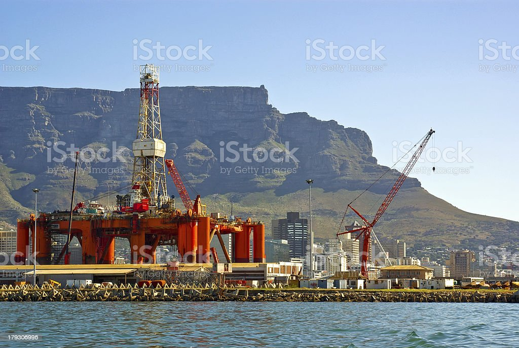 oil- rig in bay into a big city near mountains stock photo