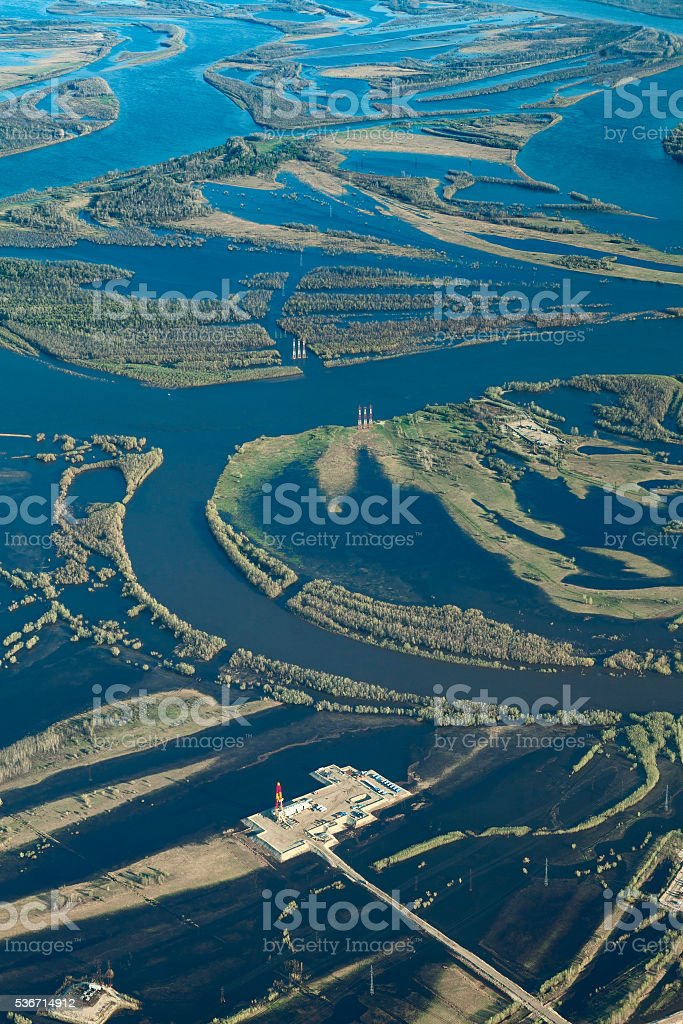 Oil rig in flooded area near great river, top view stock photo