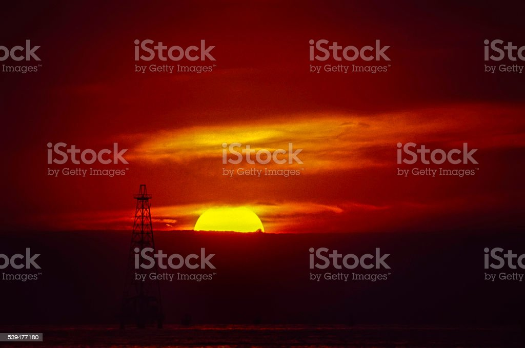 Oil rig in the sunset over water stock photo