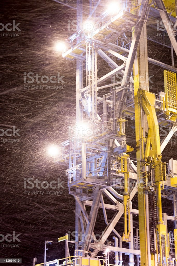oil rig platform during night  in winter snow storm stock photo