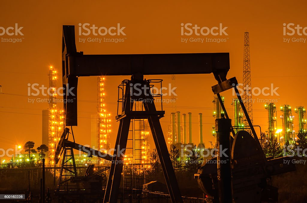 Oil rig silhouette at the background of refinery by night. stock photo