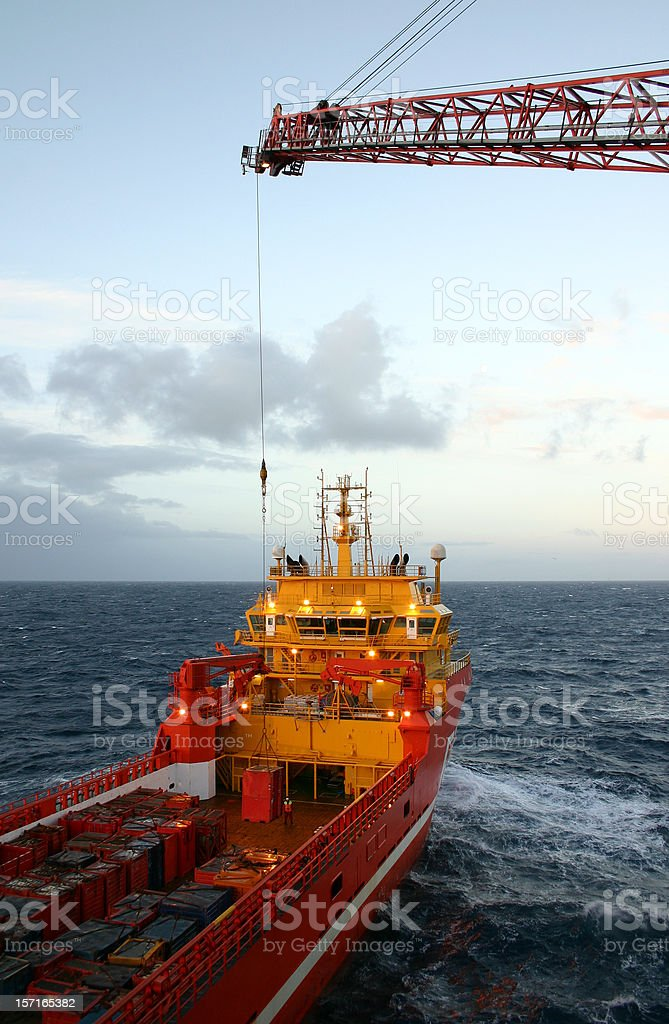 oil rig supply boat at sea with crane loading royalty-free stock photo