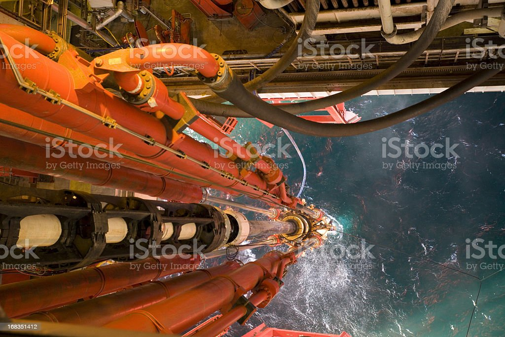 oil rig view riser pipes down to sea level stock photo