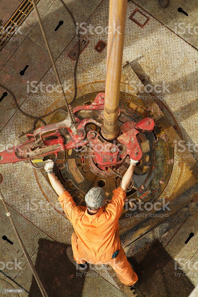 Oil rig worker dressed in orange work clothing drilling royalty-free stock photo
