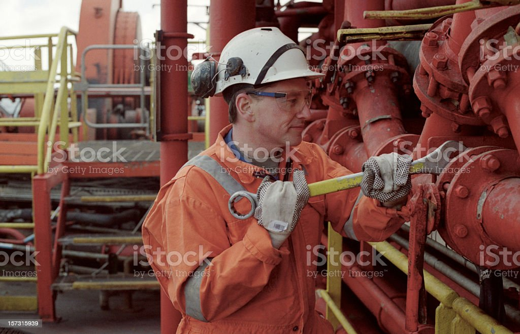 Oil rig worker fixing the pipes stock photo