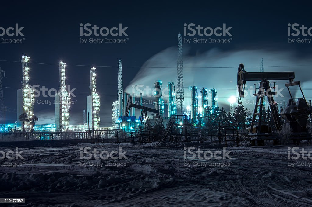 Oil rigs and brightly lit industrial site at night. stock photo