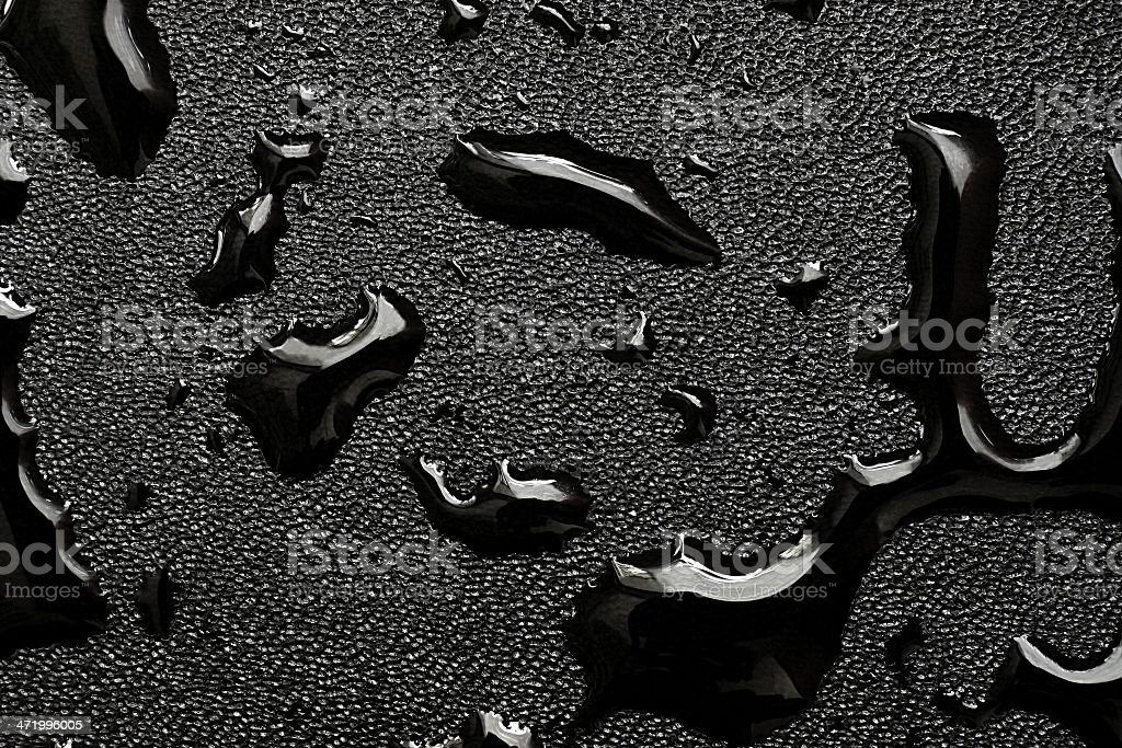 Oil slicks on black leather fabric stock photo