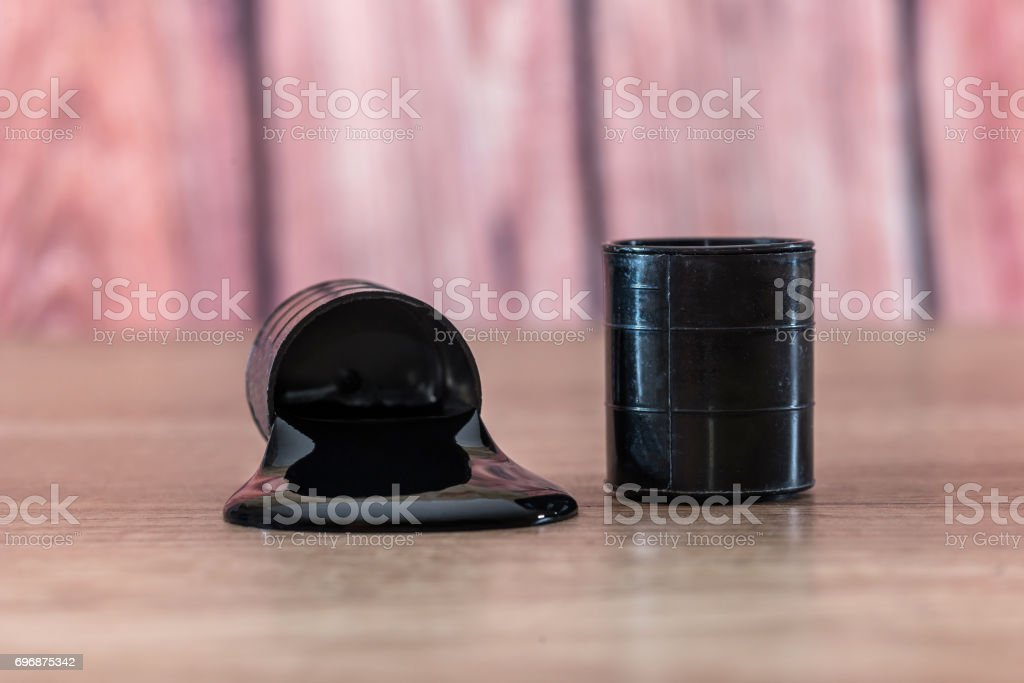 oil spilled from the barrel on wooden desk. stock photo