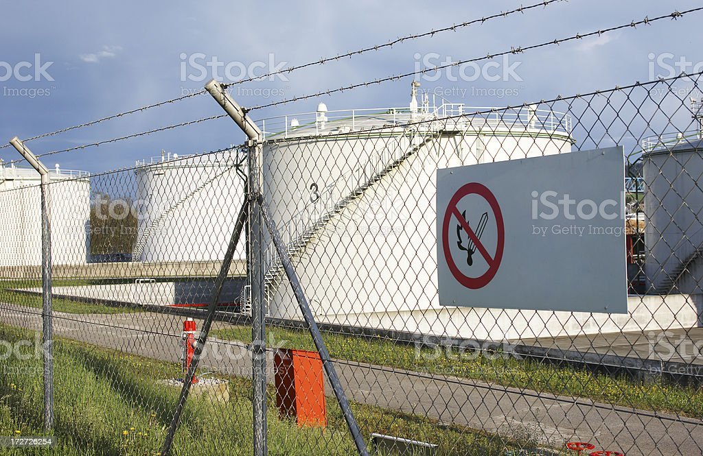 Oil station behind fence with warning sign royalty-free stock photo