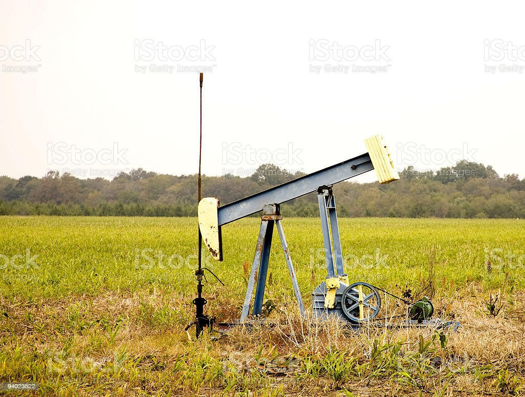 Oil Well in the midst of a farmer's field. royalty-free stock photo