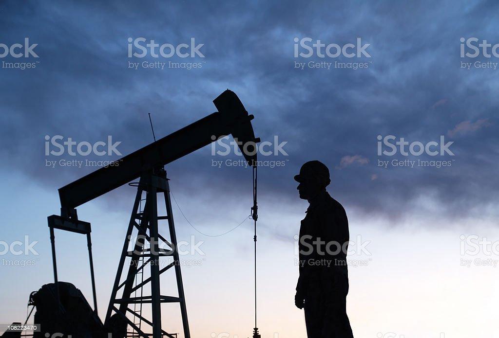 Oil Well Pumpjack & Worker Sillouhettes stock photo