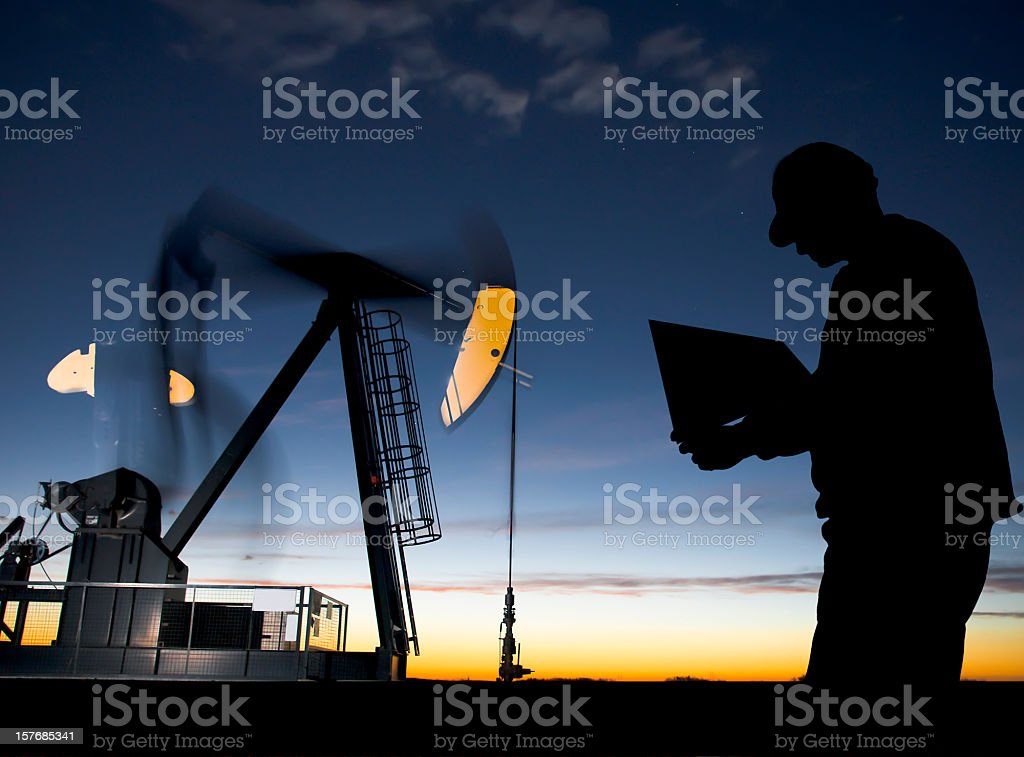 Oil Well Pumpjack at Dawn with Worker royalty-free stock photo