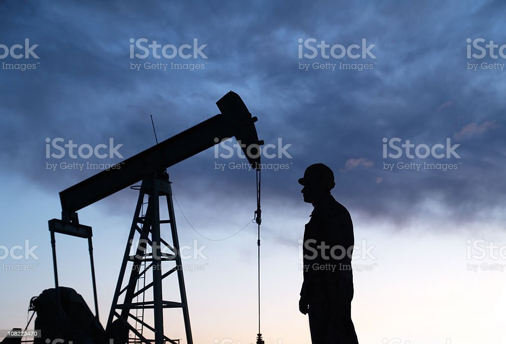 Oil Well Pumpjack & Worker Sillouhettes royalty-free stock photo