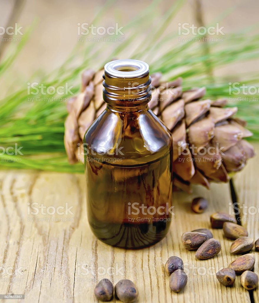 Oil with cedar cone and nuts on the board stock photo