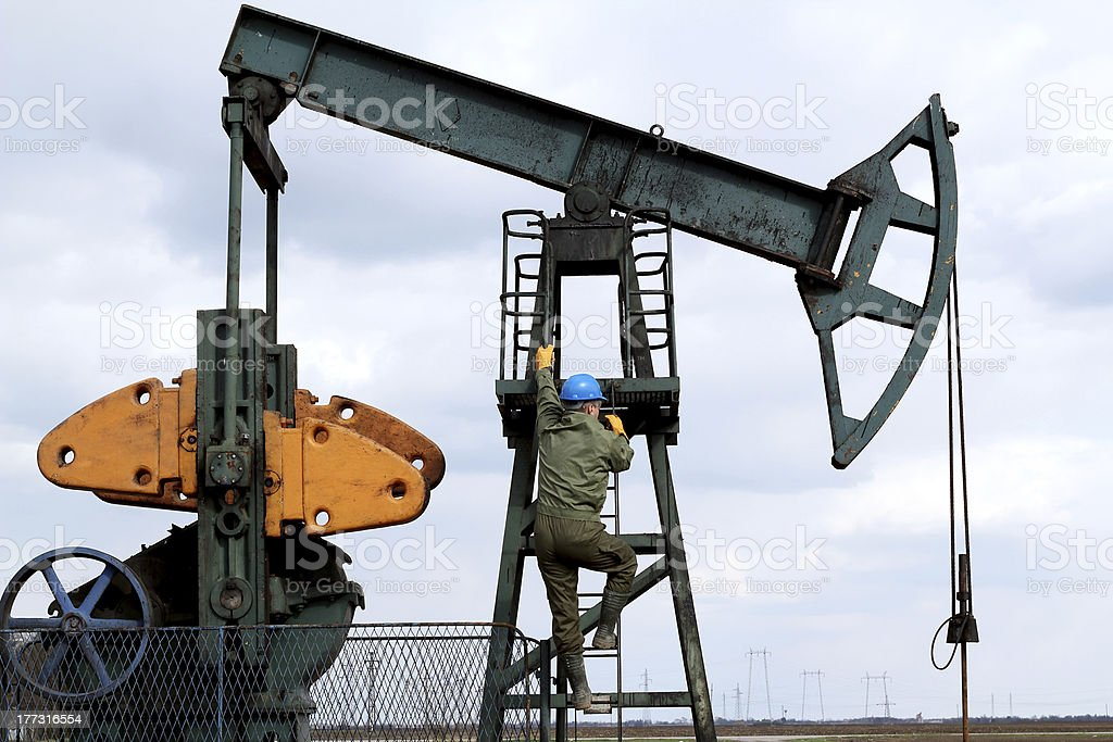 oil worker climbs to the pumpjack royalty-free stock photo