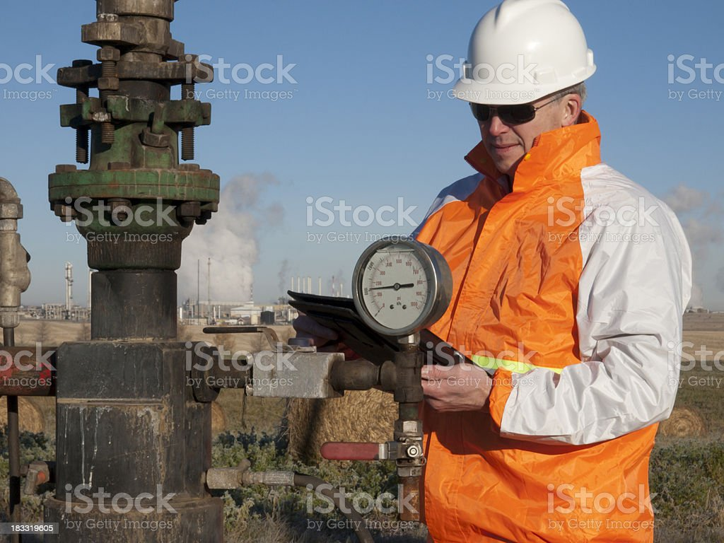 Oil Worker in Safety Gear at Well Pumpjack stock photo